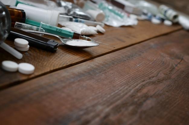 Muitas substâncias e dispositivos entorpecentes para a preparação de drogas estão sobre uma velha mesa de madeira