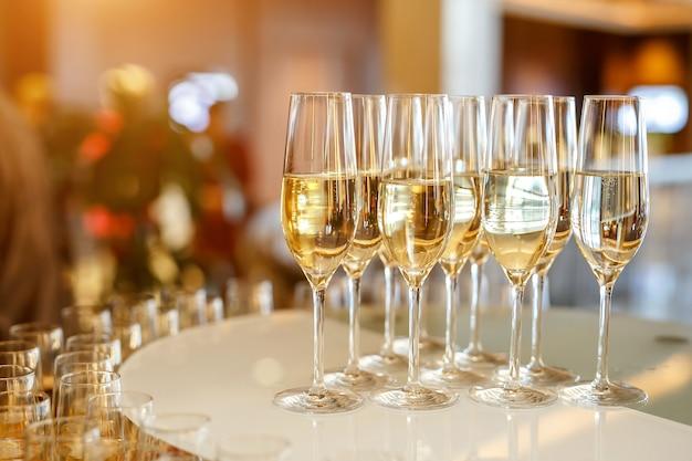 Muitas taças com champanhe ou vinho branco no catering do evento.