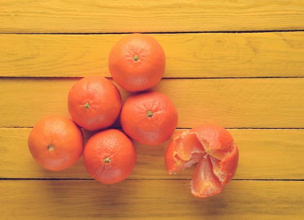 Muitas tangerinas maduras em uma mesa de madeira amarela