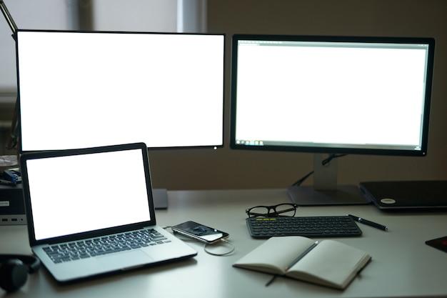 Muitas telas em branco de monitores de computador com acessórios e ferramentas de trabalho como freelance moderno