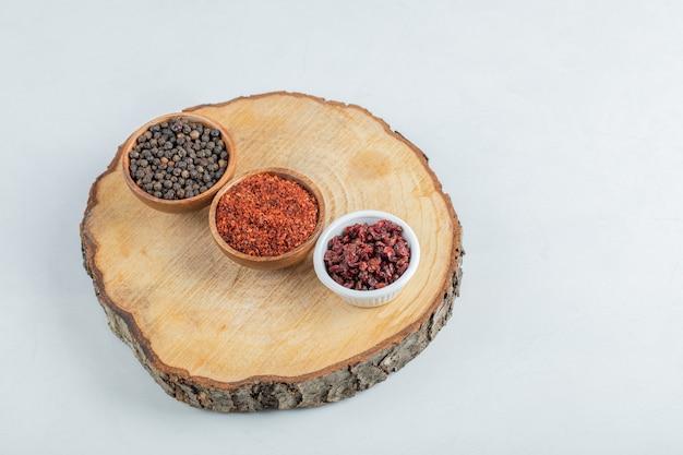 Muitas tigelas de especiarias em uma peça de madeira.