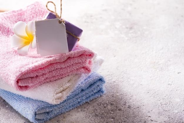 Muitas toalhas de banho coloridas empilhadas umas nas outras com sabonete e flor na pedra clara, copyspace