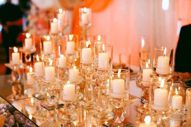 Muitas velas brancas acesas em cima da mesa