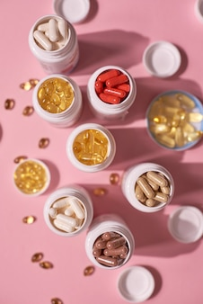 Muitas vitaminas de cápsulas de comprimidos de cor em fundo rosa. suplementos e medicamentos que fazem bem à saúde