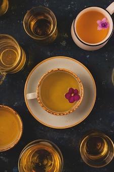 Muitas xícaras de chá com flores violetas em fundo azul escuro. layout de vista superior