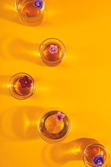 Muitas xícaras de chá transparentes diferentes com flores sobre fundo amarelo. copie o espaço