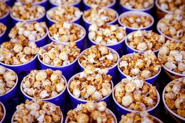 Muitas xícaras de pipoca antes do filme. vista lateral, foco seletivo