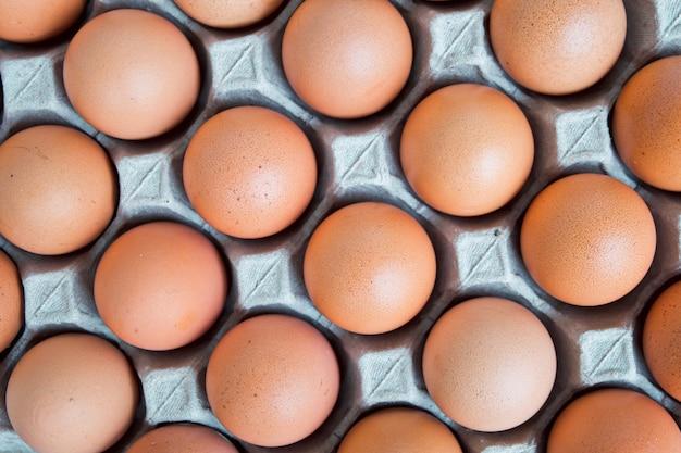 Muito a galinha crua fresca do ovo alinhou na na bandeja de papel cinzenta (pacote do cartão). flatlay
