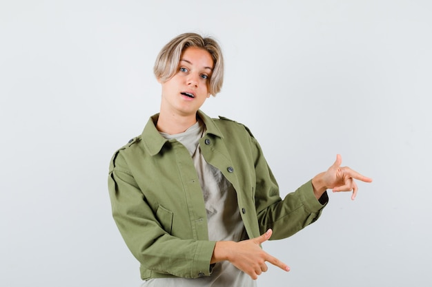 Muito adolescente apontando para a direita em uma jaqueta verde e parecendo hesitante