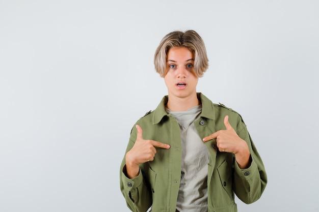Muito adolescente apontando para si mesmo com uma jaqueta verde e parecendo perplexo