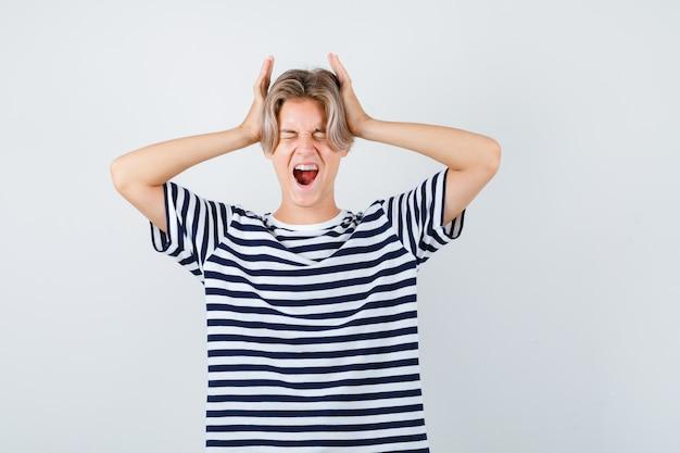 Muito adolescente com as mãos na cabeça enquanto grita em uma camiseta listrada e parece agressivo. vista frontal.