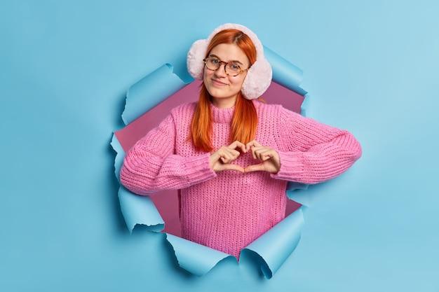 Muito adolescente com cabelo ruivo natural usa aquecedores de orelha de inverno e suéter tricotado formas gesto de coração expressa amor.
