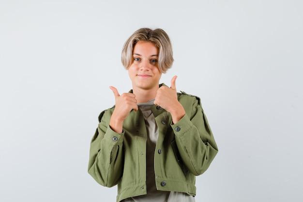Muito adolescente mostrando os polegares duplos na jaqueta verde e parecendo alegre. vista frontal.