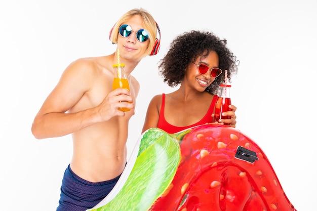 Muito africano feminino e caucasiano loiro fica de maiô com colchões de borracha praia, bebe suco e ouve música isolada na parede branca