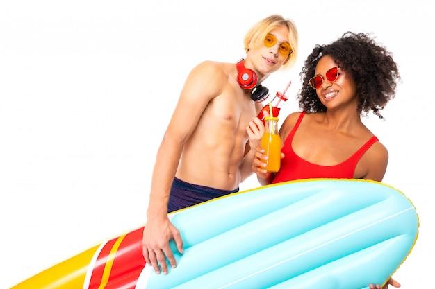 Muito africano feminino e caucasiano loiro fica de maiô com colchões de borracha praia, bebe suco e sorrisos, isolados na parede branca