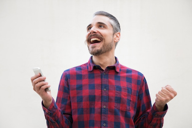 Muito animado homem animado com celular fazendo gesto de vencedor
