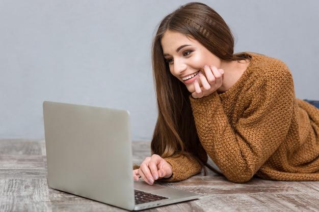 Muito atraente, doce alegre jovem mulher com cabelo comprido em um suéter marrom deitado no chão de madeira usando laptop