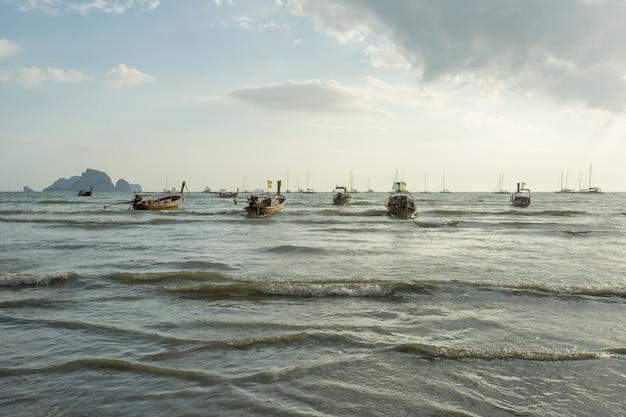 Muito barco de cauda longa atrás de mergulhar na praia de ao nang antes do pôr-do-sol
