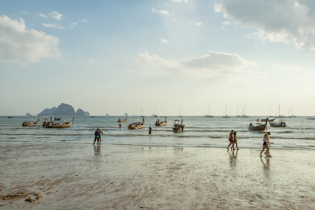 Muito barco de rabo longo atrás de mergulhar na praia de ao nang