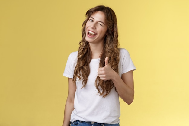 Muito bem, companheiro. alegre extrovertido atrevido atraente mulher de cabelos cacheados wink sorrindo aceno de aprovação mostrar polegares para cima como sua escolha bom trabalho aceitar os termos suporte fundo amarelo