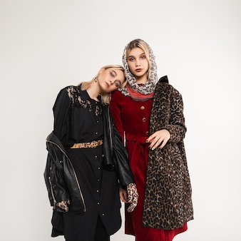 Muito bem jovem elegante modelo em leopardo glamouroso casaco de pele elegante com lenço e mulher com jaqueta de couro preta perto de parede vintage dentro de casa