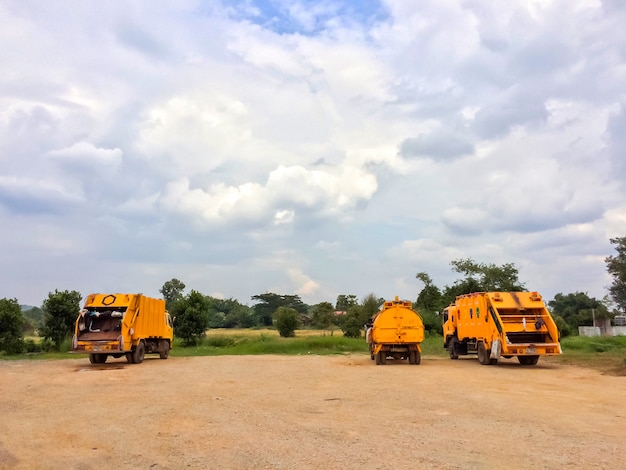 Muito caminhão de lixo amarelo com céu azul e nuvens.