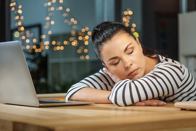 Muito cansado. pacífica, exausta, trabalhadora e trabalhadora, sentada à secretária e adormecendo enquanto trabalha