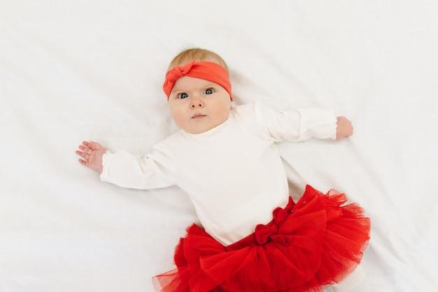 Muito caucasiano bebê menina vestindo saia vermelha e faixa correspondente