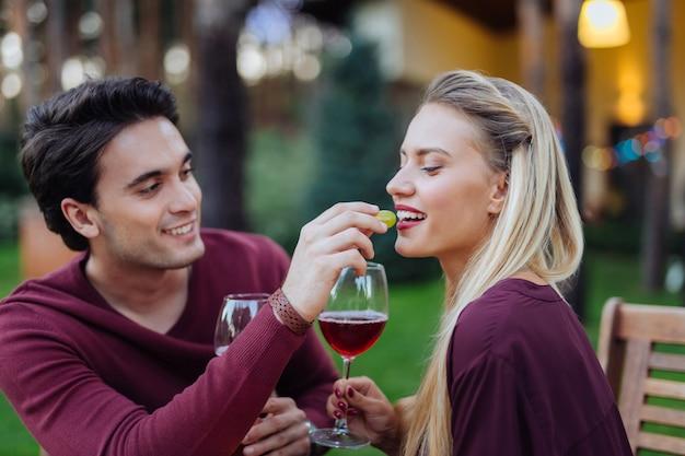 Muito deliciosa. mulher jovem e bonita sorrindo enquanto come das mãos do namorado