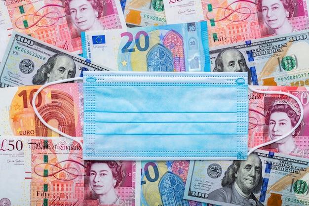 Muito dinheiro em diferentes moedas no fundo com máscara protetora como símbolo da pandemia