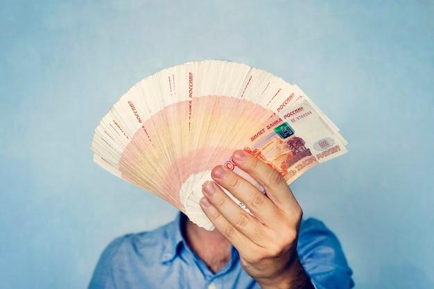 Muito dinheiro na mão de um jovem empresário sobre um fundo azul. uma pilha de notas de banco de rublos russos com valor nominal de 5.000 rublos. empresário de sucesso