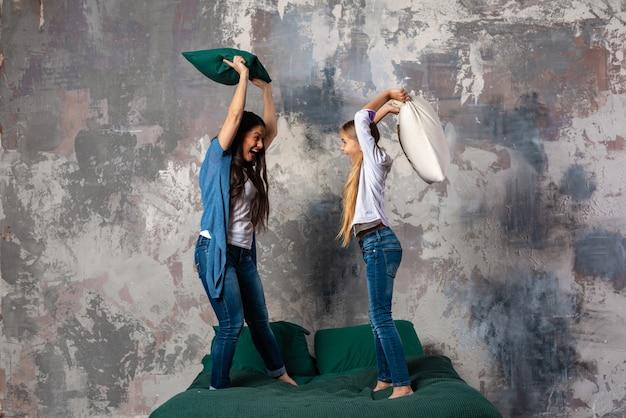 Muito divertido mãe e sua filha pequena brigam com travesseiros na cama em pé