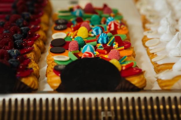 Muito doce. deliciosos éclairs frescos decorados com doces coloridos colocados próximos uns dos outros em exibição