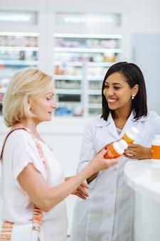 Muito espirituoso. mulher loira atenta em pé na semi-posição e olhando para a garrafa com vitaminas