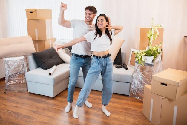Muito feliz casal jovem dança na sala de estar perto de caixas de papelão entreter no dia da mudança, feliz marido e mulher se divertir balançar redemoinho se mudar para o próprio apartamento juntos, conceito de realocação