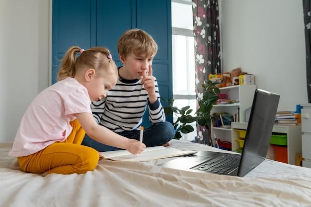 Muito feliz fazendo lição de casa em casa usando laptop