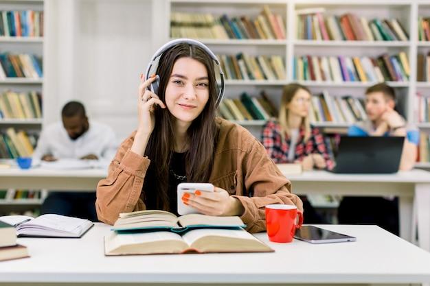 Muito feliz sorridente jovem aluna em roupas casuais hipster, sentado na biblioteca e ouvindo boa música em fones de ouvido,