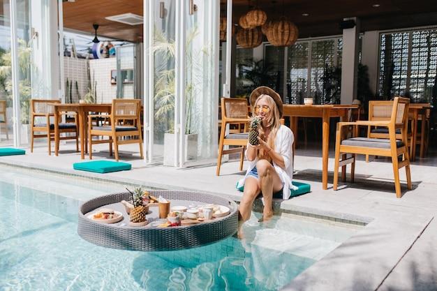 Muito feminina turista bebendo coquetel no café do resort de manhã.