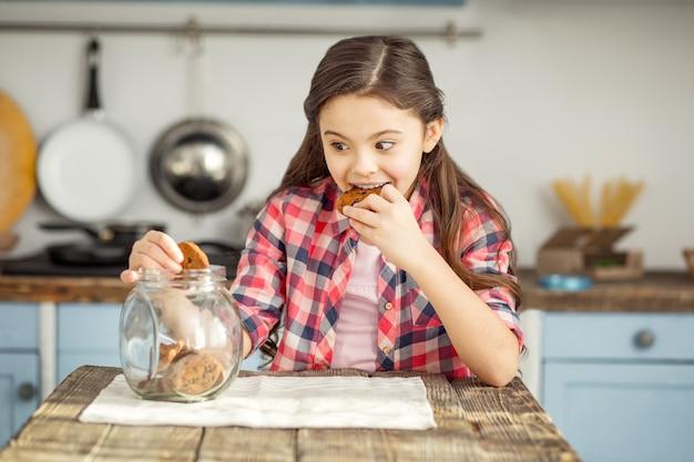 Muito gostoso. garotinha de cabelos escuros bem alegre sentada à mesa comendo um biscoito e pegando mais um pouco