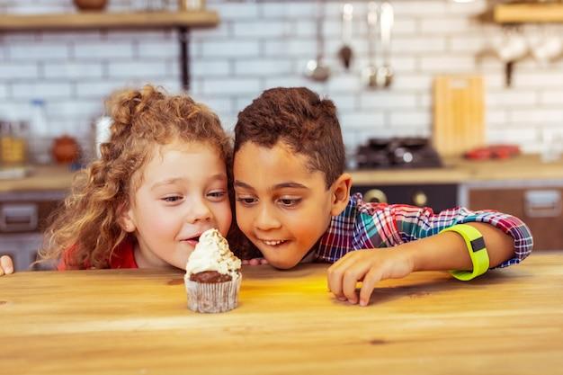 Muito gostoso. menino alegre com um sorriso no rosto enquanto olha para o bolo