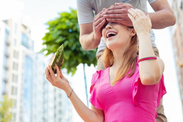 Muito gostoso. mulher simpática e encantada segurando uma fatia de melancia enquanto espera por uma surpresa do namorado