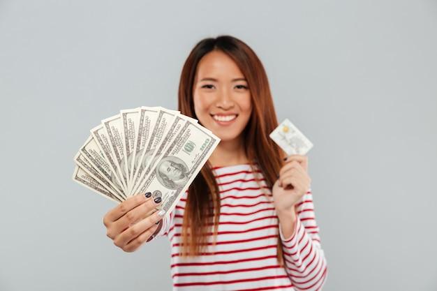 Muito jovem asiática segurando dinheiro e cartão de crédito.
