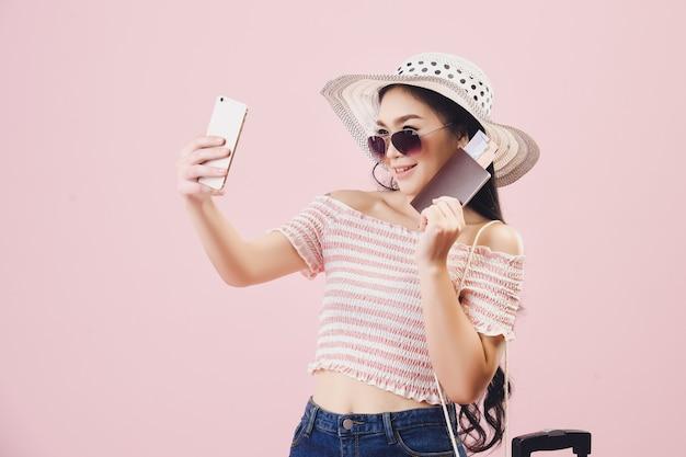 Muito jovem asiática sorrindo usa óculos escuros e tira uma selfie por smartphone, mochileiro de mulheres jovens tira uma selfie e segurando o passaporte em fundo rosa de estúdio. filtros de tom rosa pastel.