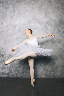 Muito jovem bailarina dançando balé clássico contra parede rústica