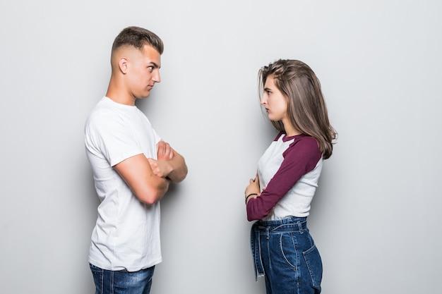 Muito jovem casal bonito, menino e menina olhando com raiva um do outro, isolado no branco