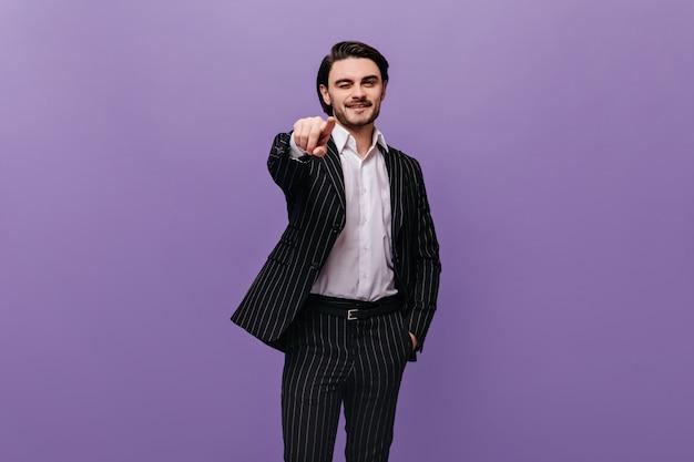 Muito jovem com cabelo castanho, camisa clara e terno listrado escuro olhando e apontando para a frente, isolado na parede violeta