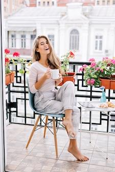 Muito jovem com cabelo comprido, tomando café da manhã na varanda pela manhã. ela segura uma xícara e está sorrindo.