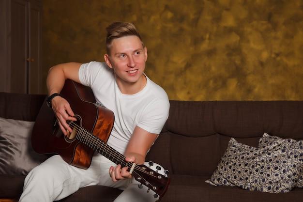 Muito jovem com guitarra no interior da sala. homem fofo no sofá com guitarra