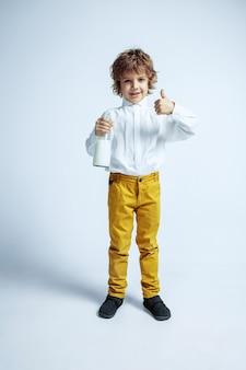 Muito jovem com roupas casuais na parede branca. posando na moda. pré-escolar do sexo masculino, caucasiano, com emoções faciais brilhantes. infância, expressão, diversão. bebendo leite, polegar para cima.