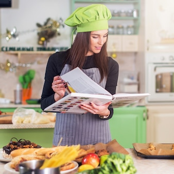 Muito jovem cozinheira usando chapéu de chef à procura de uma receita no livro de receitas em pé na cozinha